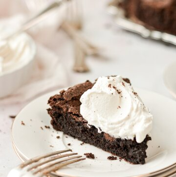A slice of flourless chocolate cake topped with bourbon whipped cream.