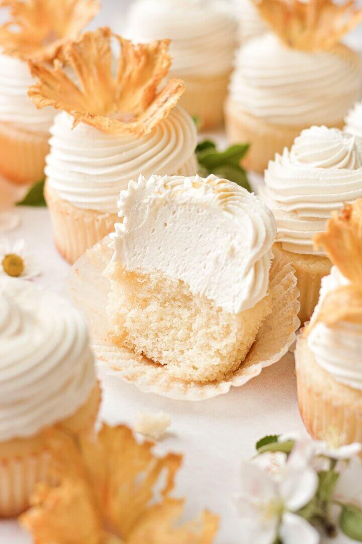 A honey lemon cupcake with a bite taken.