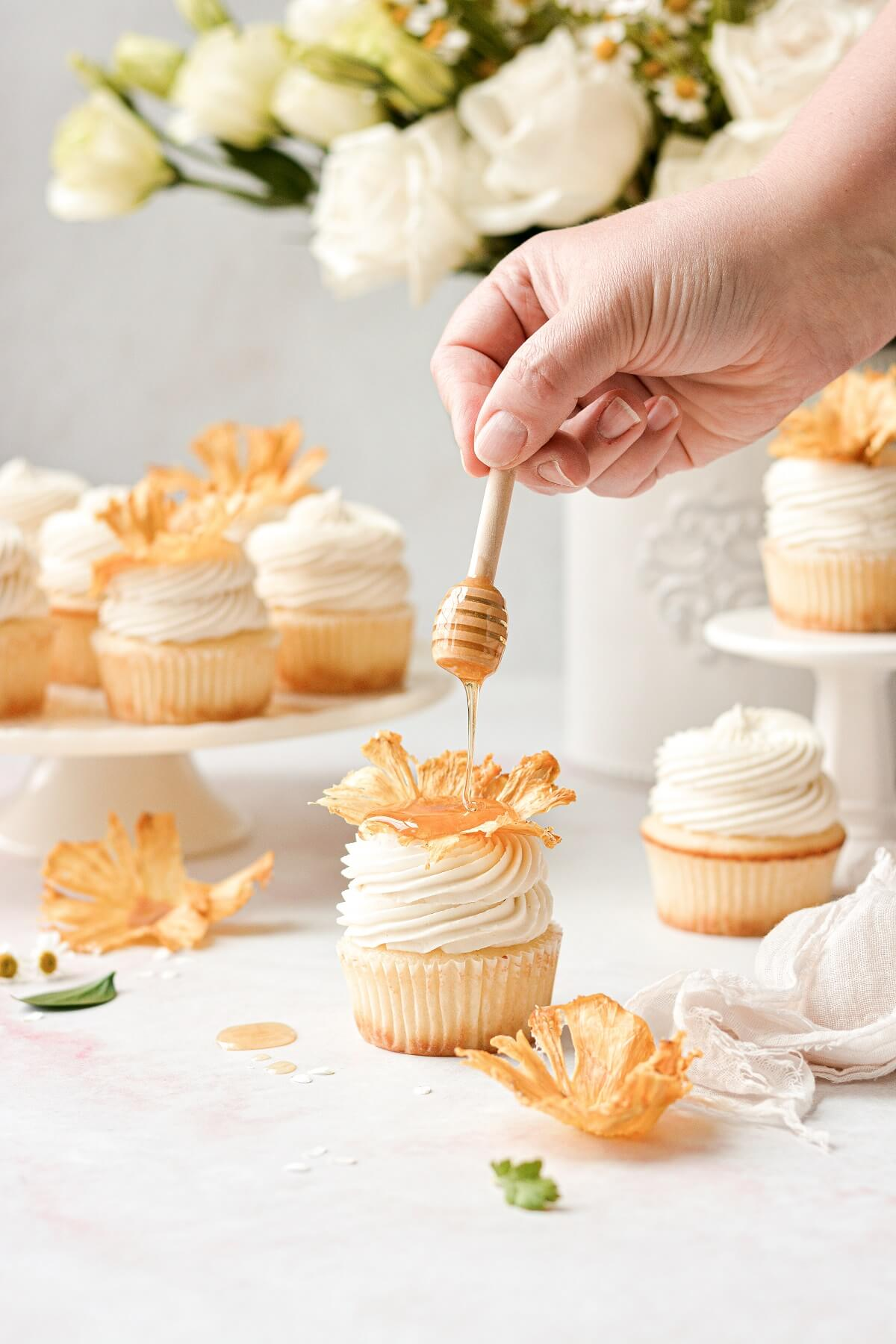 Honey being drizzled over a honey lemon cupcake.