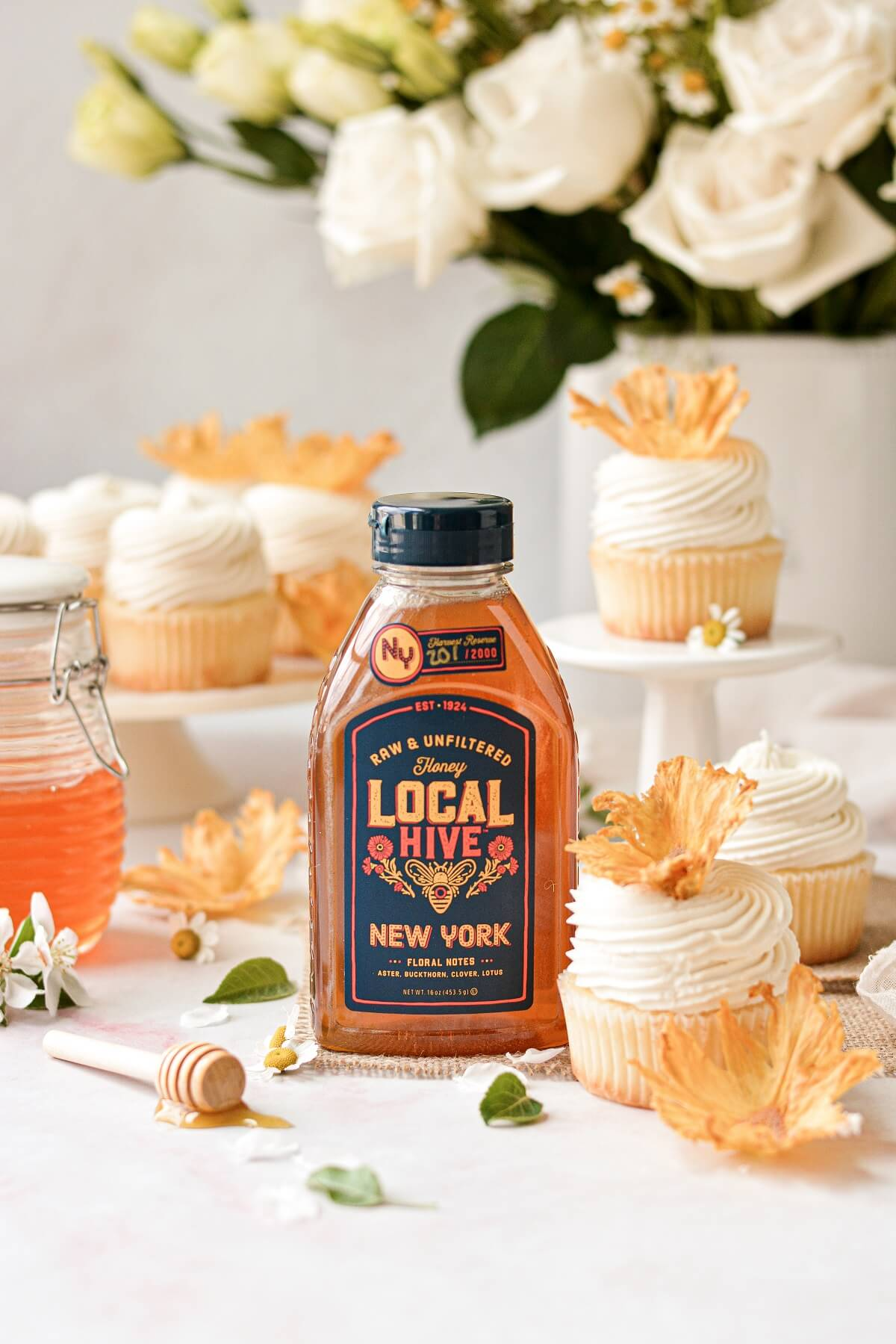 A bottle of Local Hive honey from New York, surrounded by honey lemon cupcakes.
