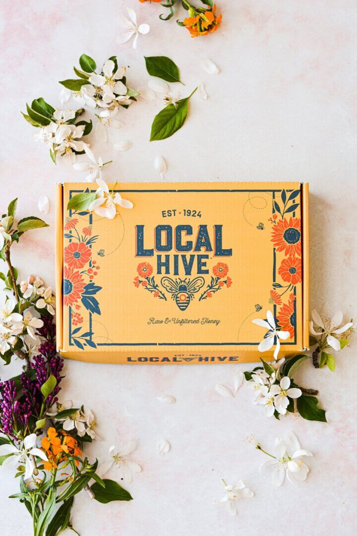 A yellow product box from Local Hive honey, surrounded by wildflowers.
