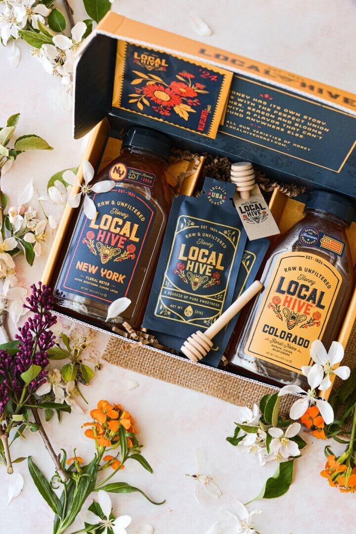 Bottles of Local Hive honey surrounded by wildflowers.