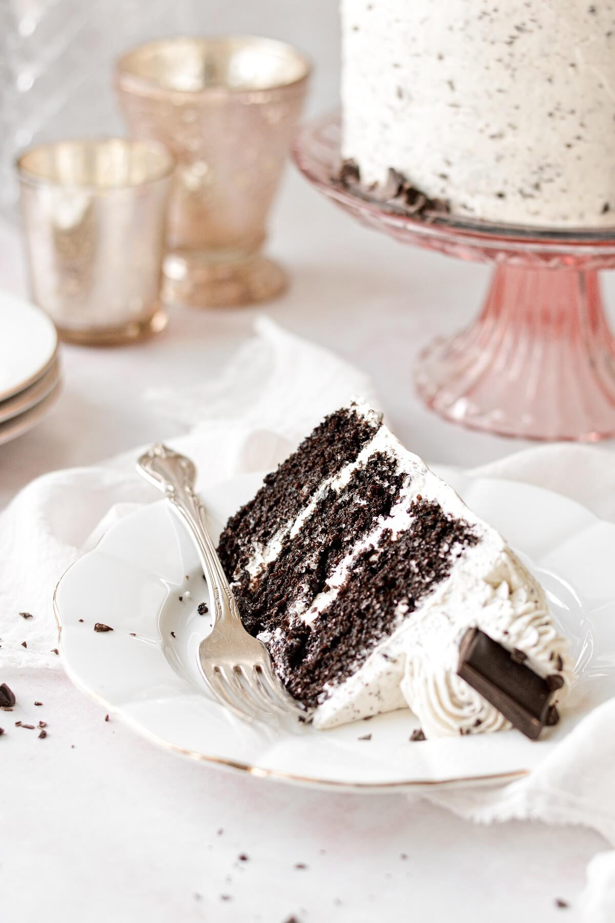A slice of mint chocolate chip cake on a white plate.