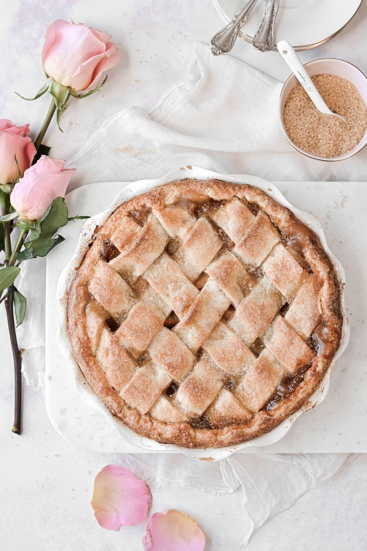 Peach pie with a lattice crust, next to pink roses.