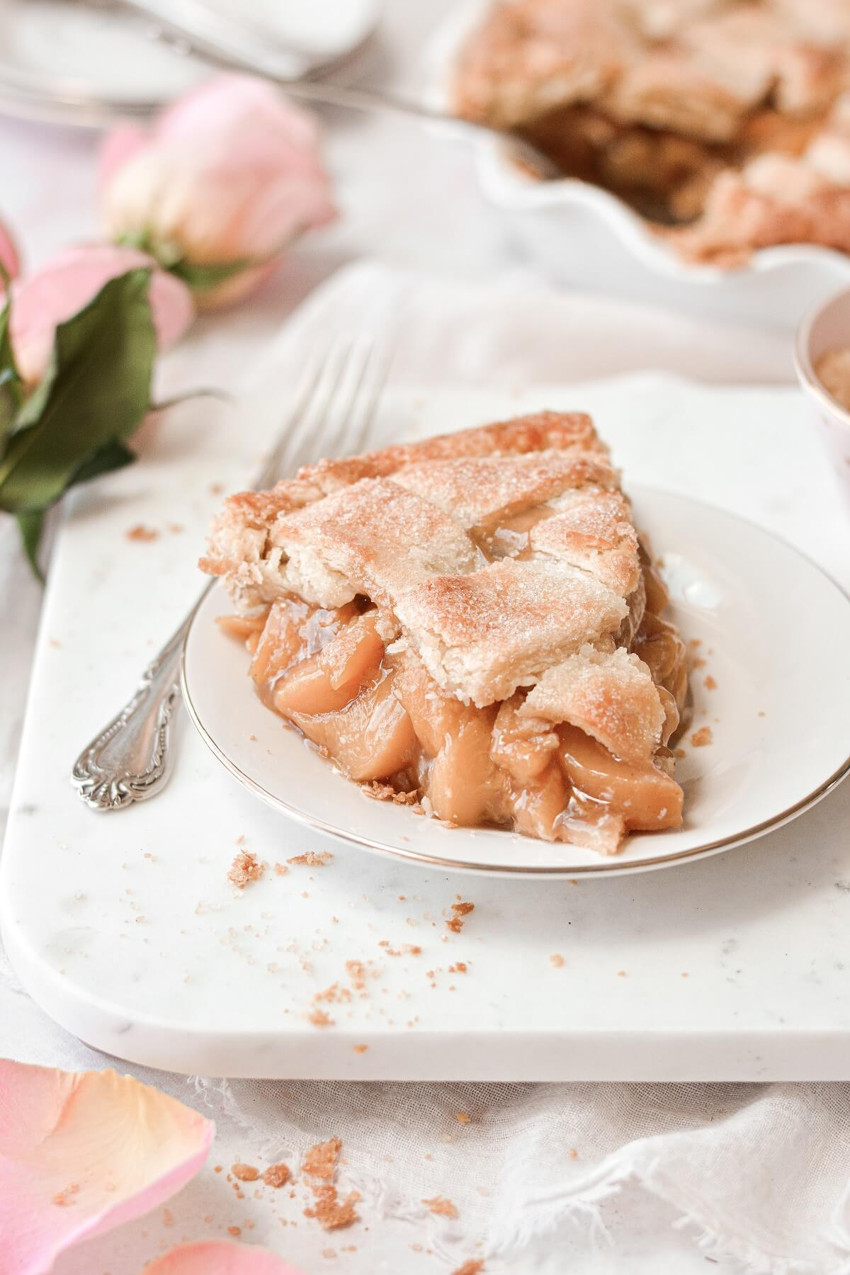 A slice of peach pie on a white marble serving board.