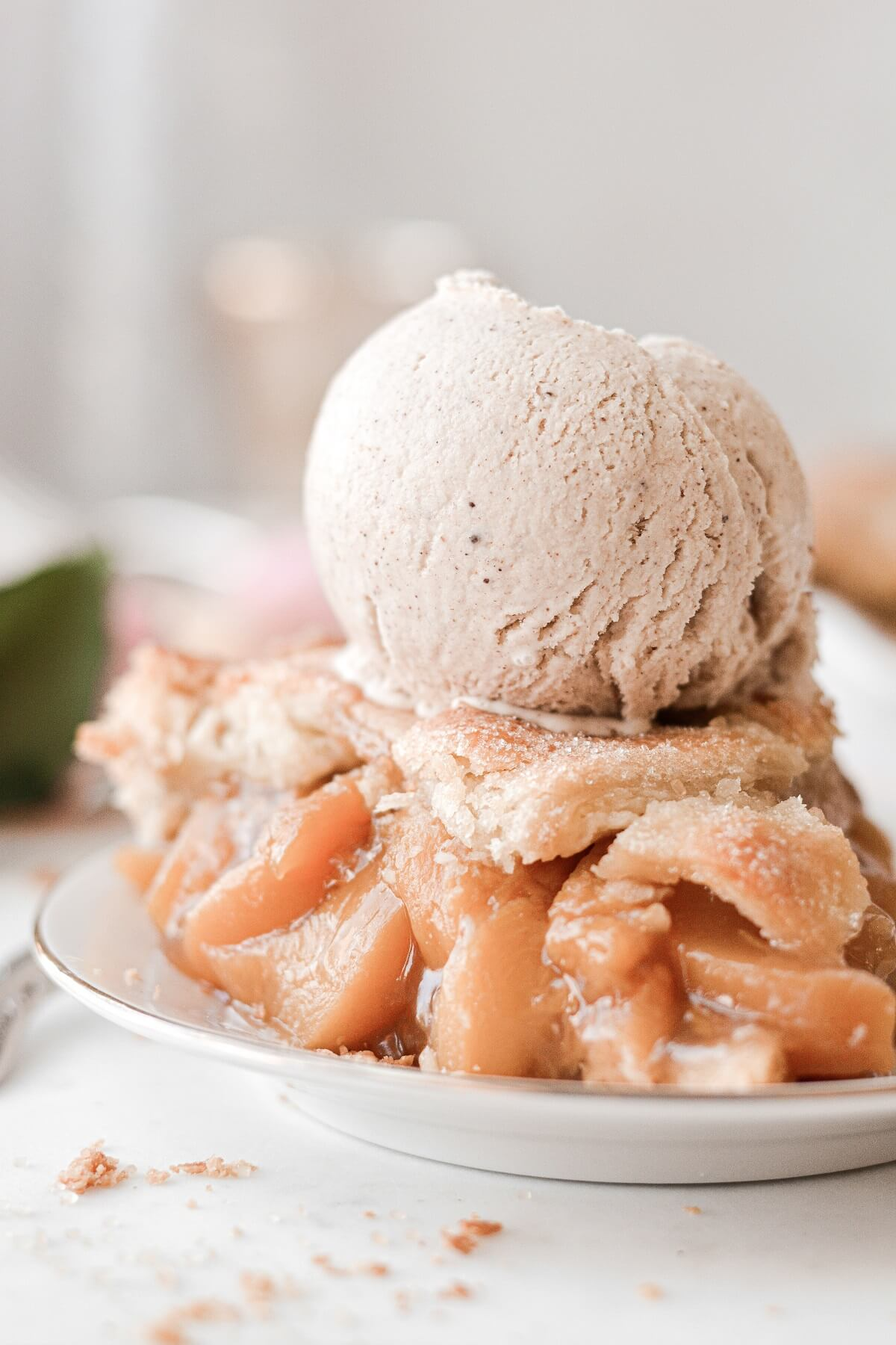 A slice of peach pie topped with a scoop of cinnamon ice cream.