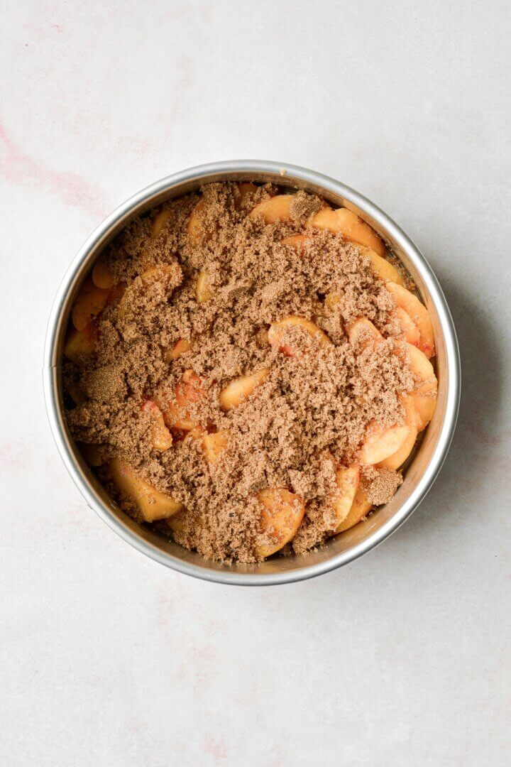 Sliced peaches topped with brown sugar in a cake pan.