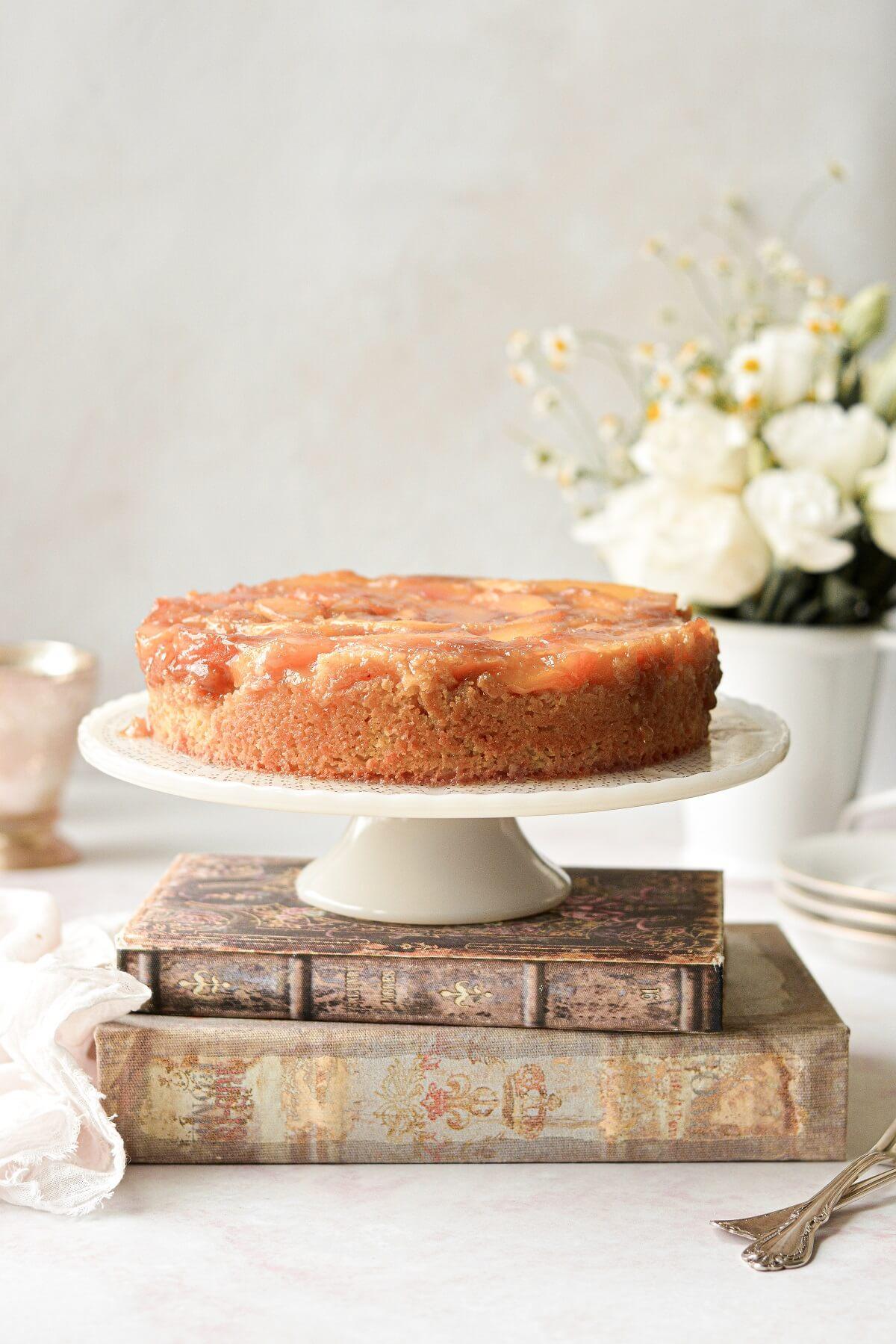 Peach upside down cake on a cake pedestal.