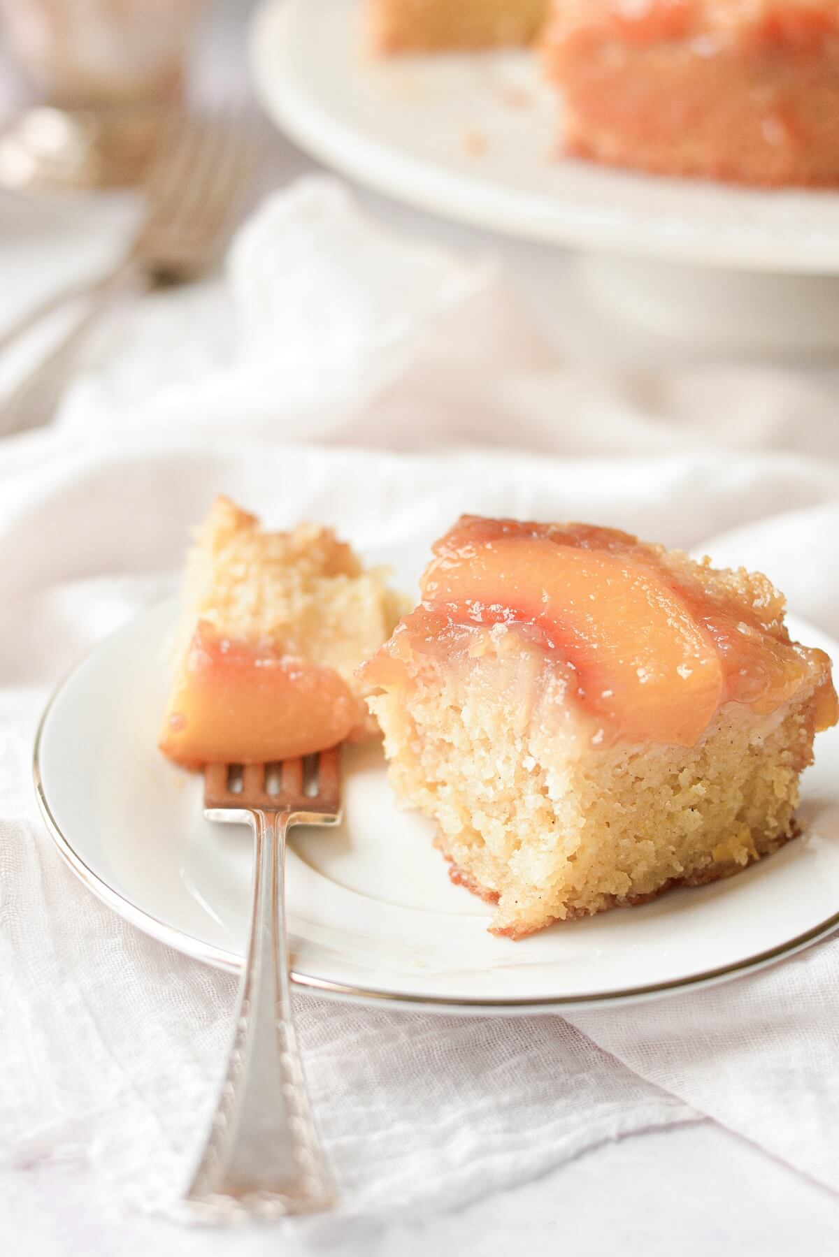 A slice of peach upside down cake with a bite taken.