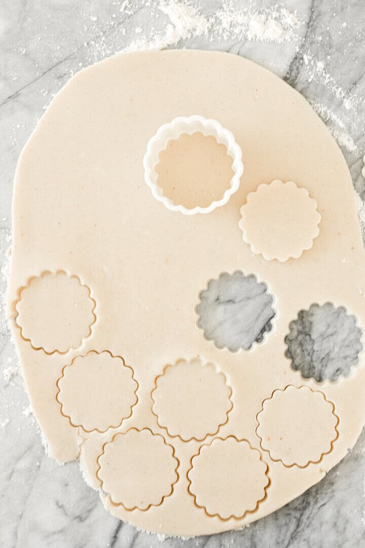 Shortbread cookie dough on a marble slab, rolled out and cut into cookies.