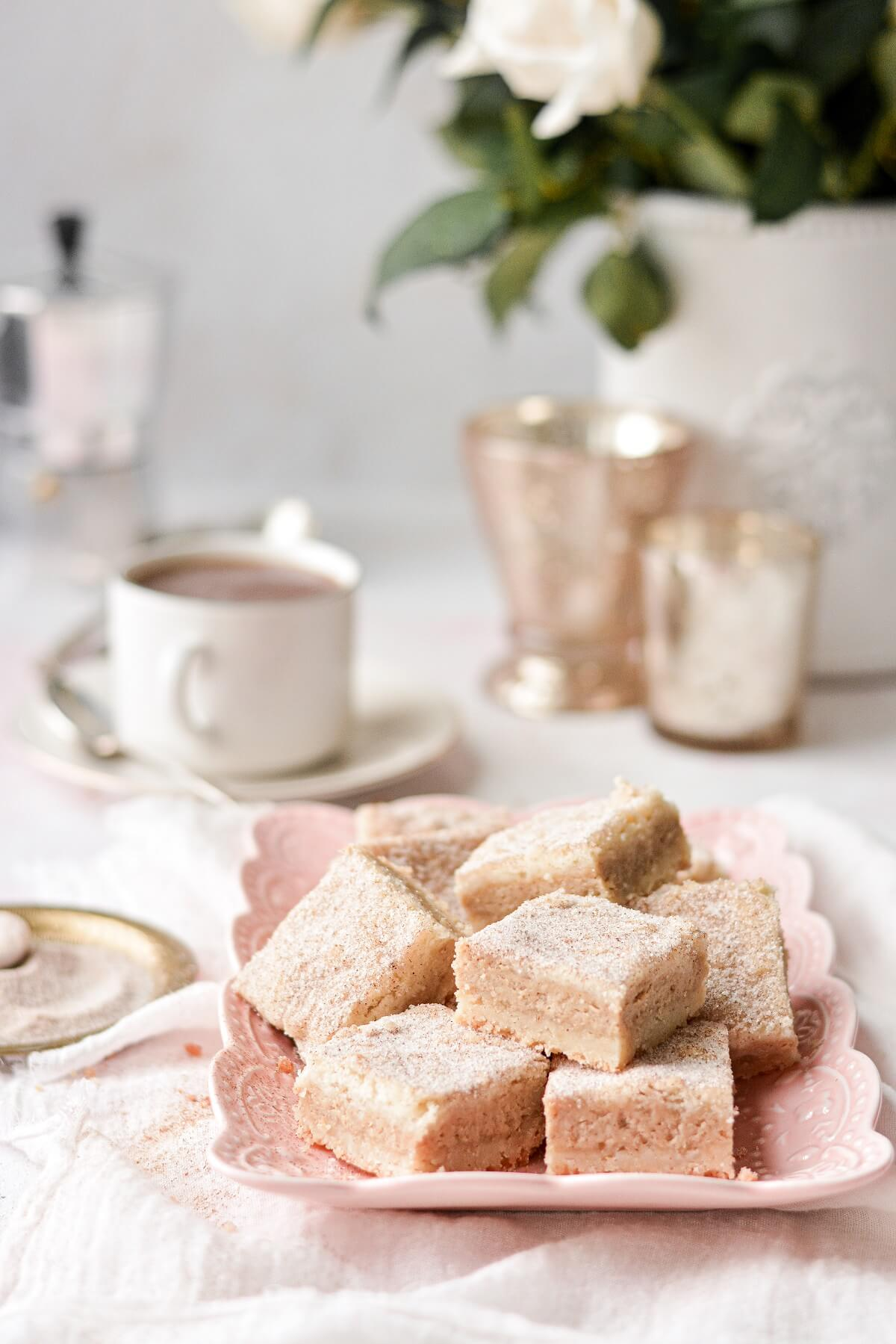 Snickerdoodle cheesecake shortbread bars arranged on a pink plate.