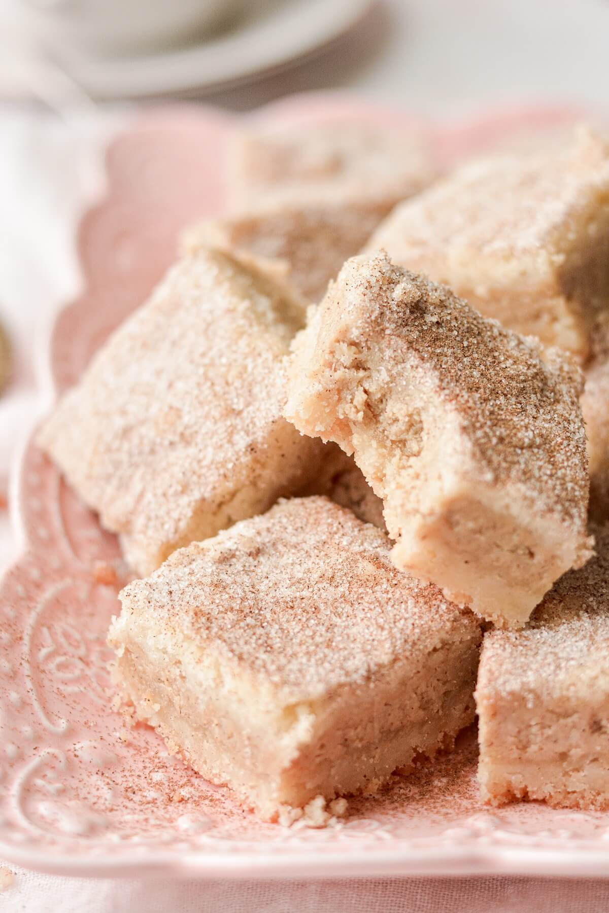 Snickerdoodle cheesecake shortbread bars, one with a bite taken, arranged on a pink plate.