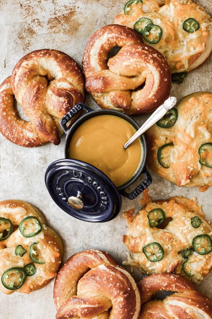 Soft pretzels on a baking sheet, with a pot of mustard for dipping.