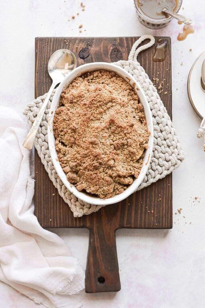 Apple caramel crumble on a wooden cutting board.