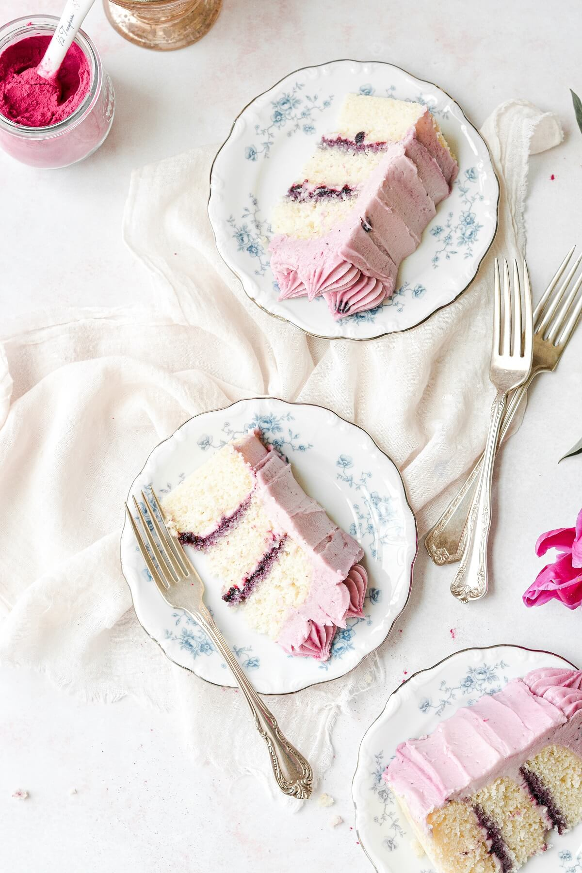 Slices of vanilla cake with blueberry jam filling and blueberry buttercream.