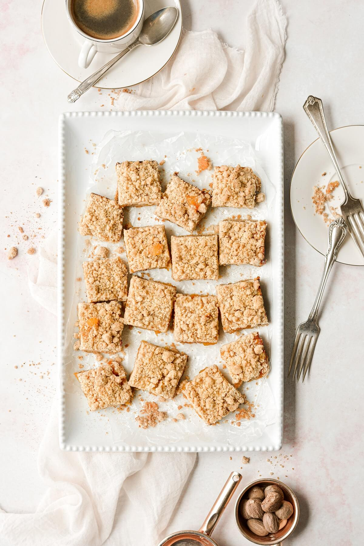 Peach crumb bars on a white platter, with a cup of coffee.