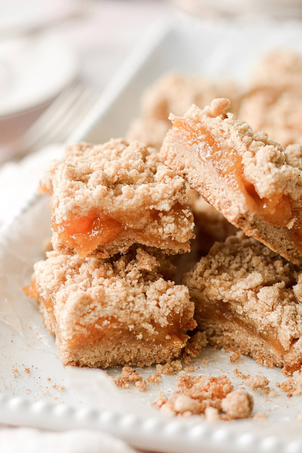 Peach crumb bars stacked on a white platter.
