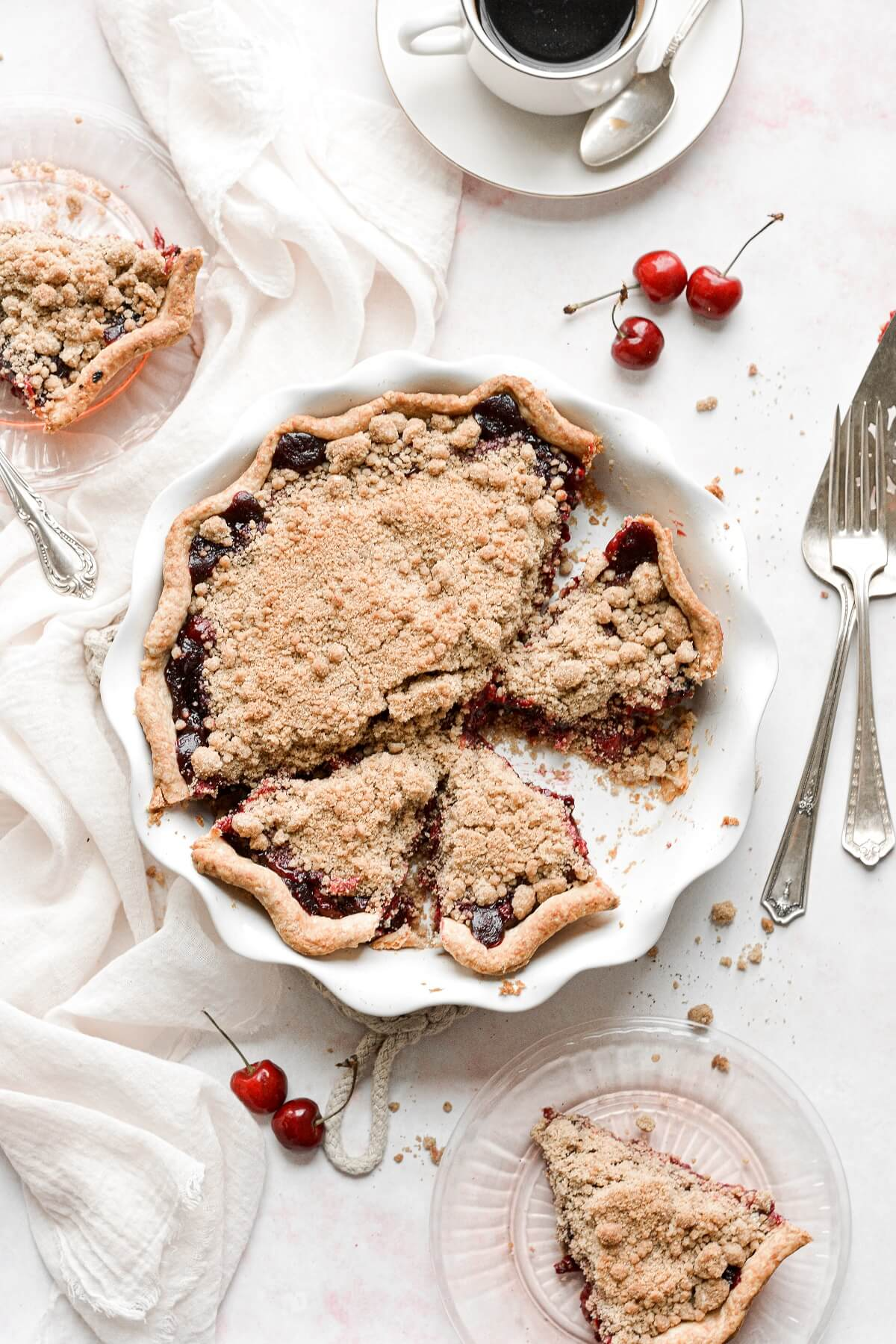 Cherry crumb pie with several slices cut.