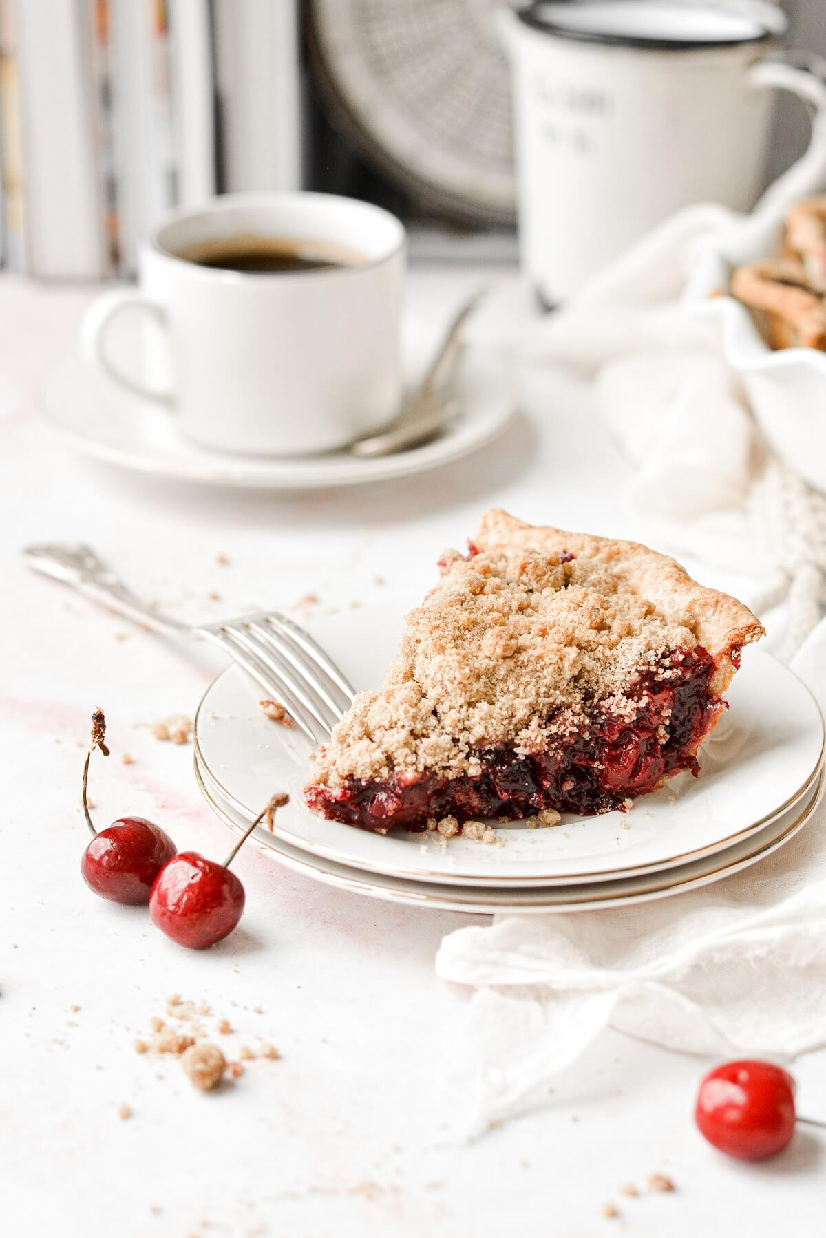 A slice of cherry crumb pie with a cup of coffee.