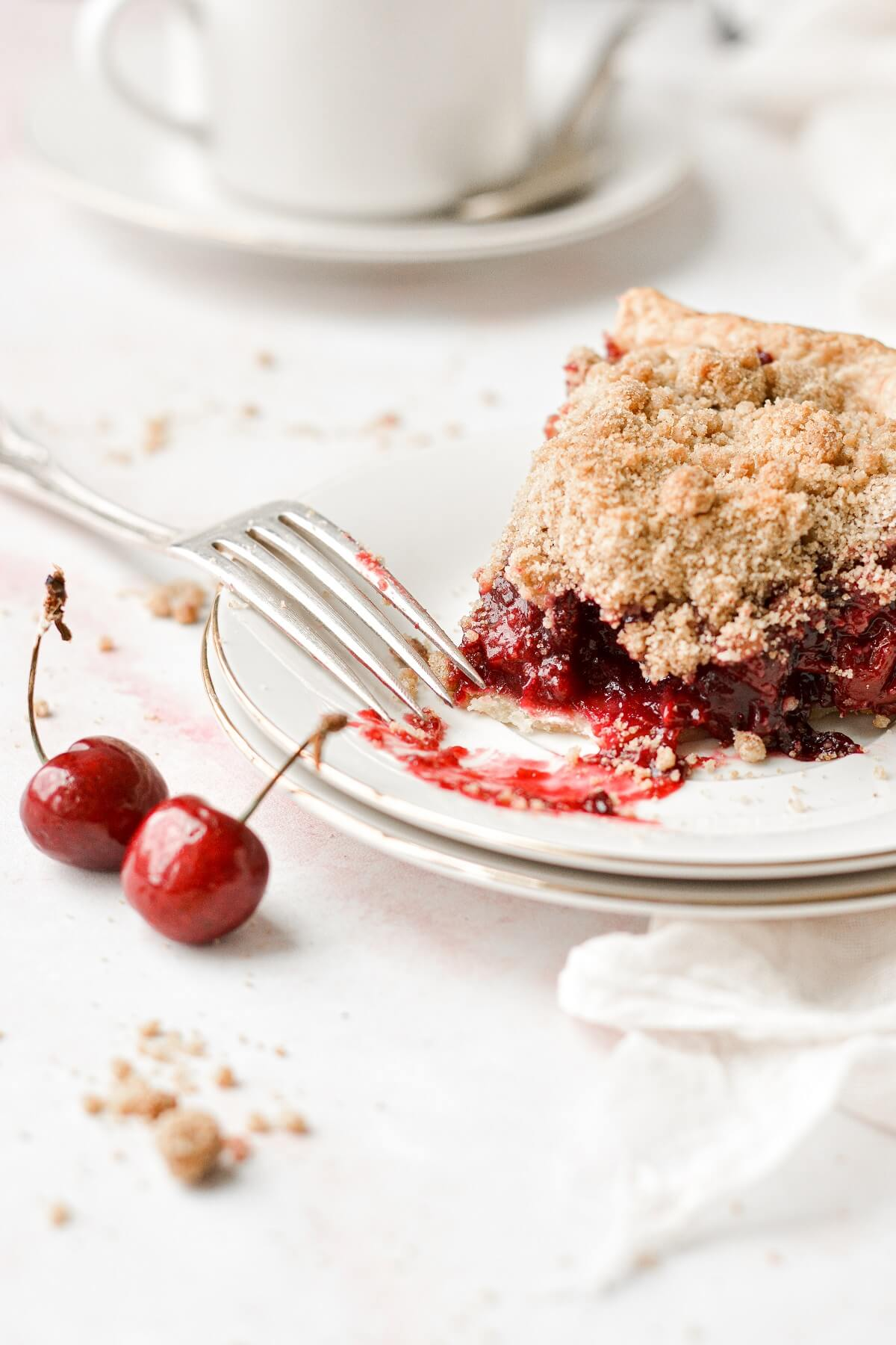 A slice of cherry crumb pie with a bite taken.