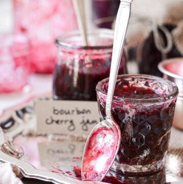 Glass jars filled with homemade bourbon cherry jam, and a spoon covered in jam.