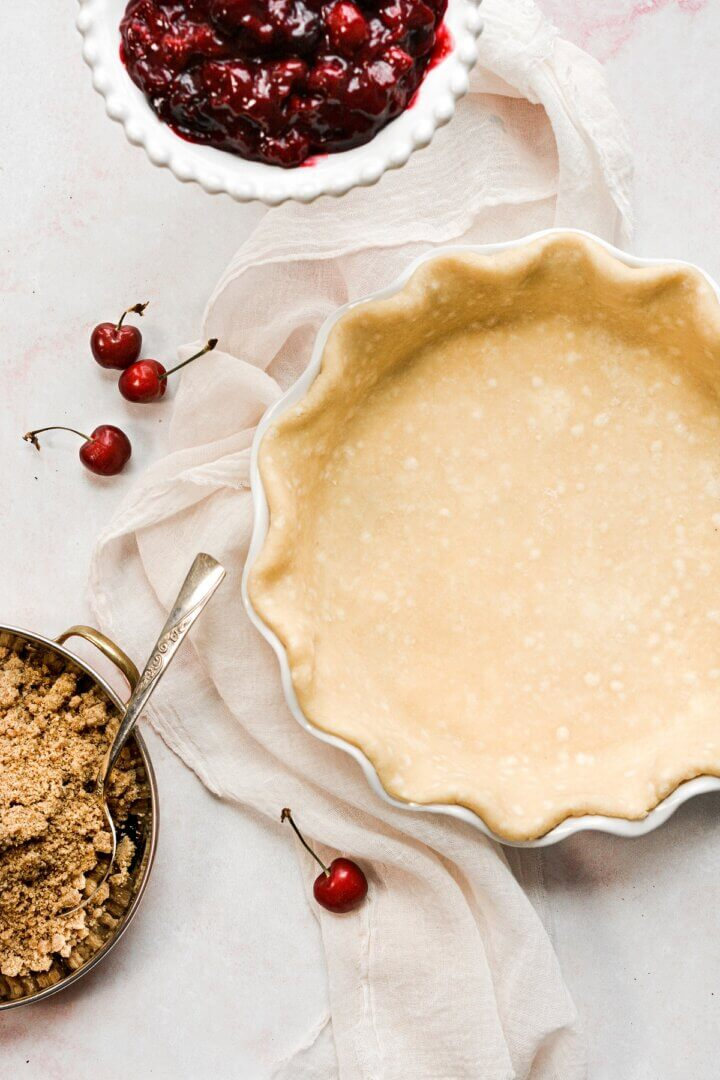 An unbaked pie crust, with bowls of cherry pie filling and crumb topping.