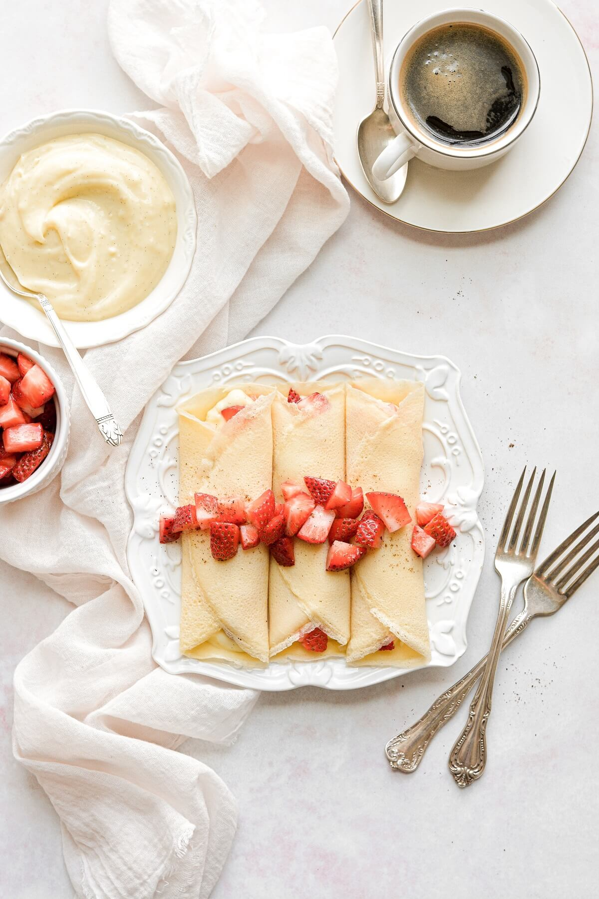 Three homemade crepes, topped with strawberries.
