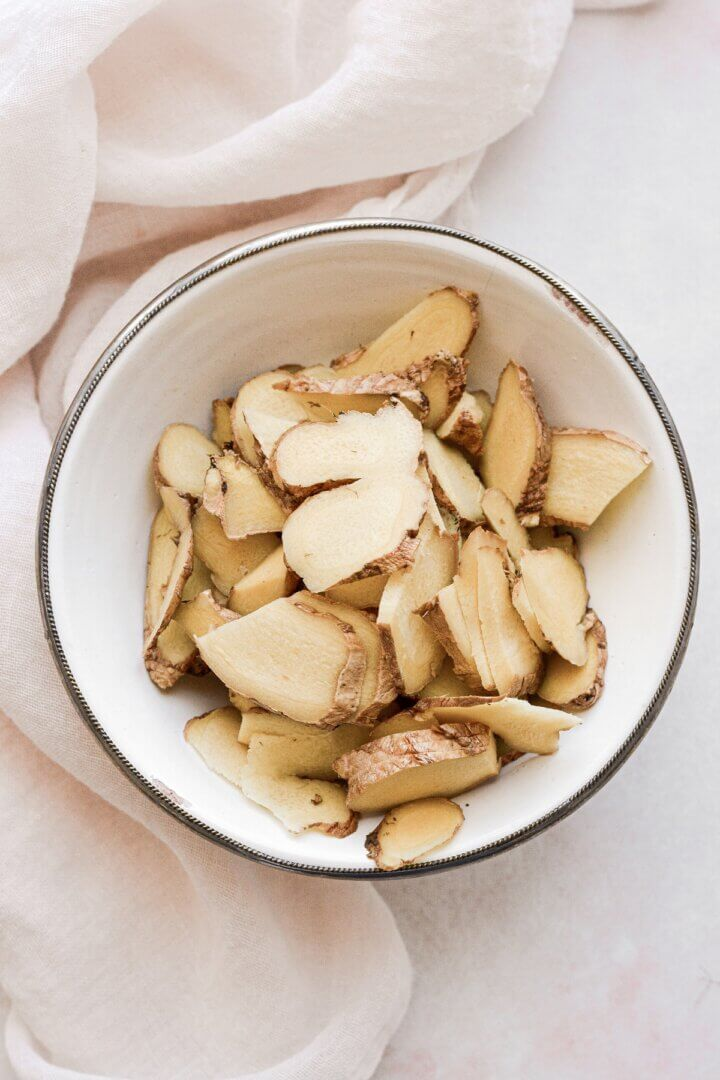 Slices of fresh ginger in a bowl.