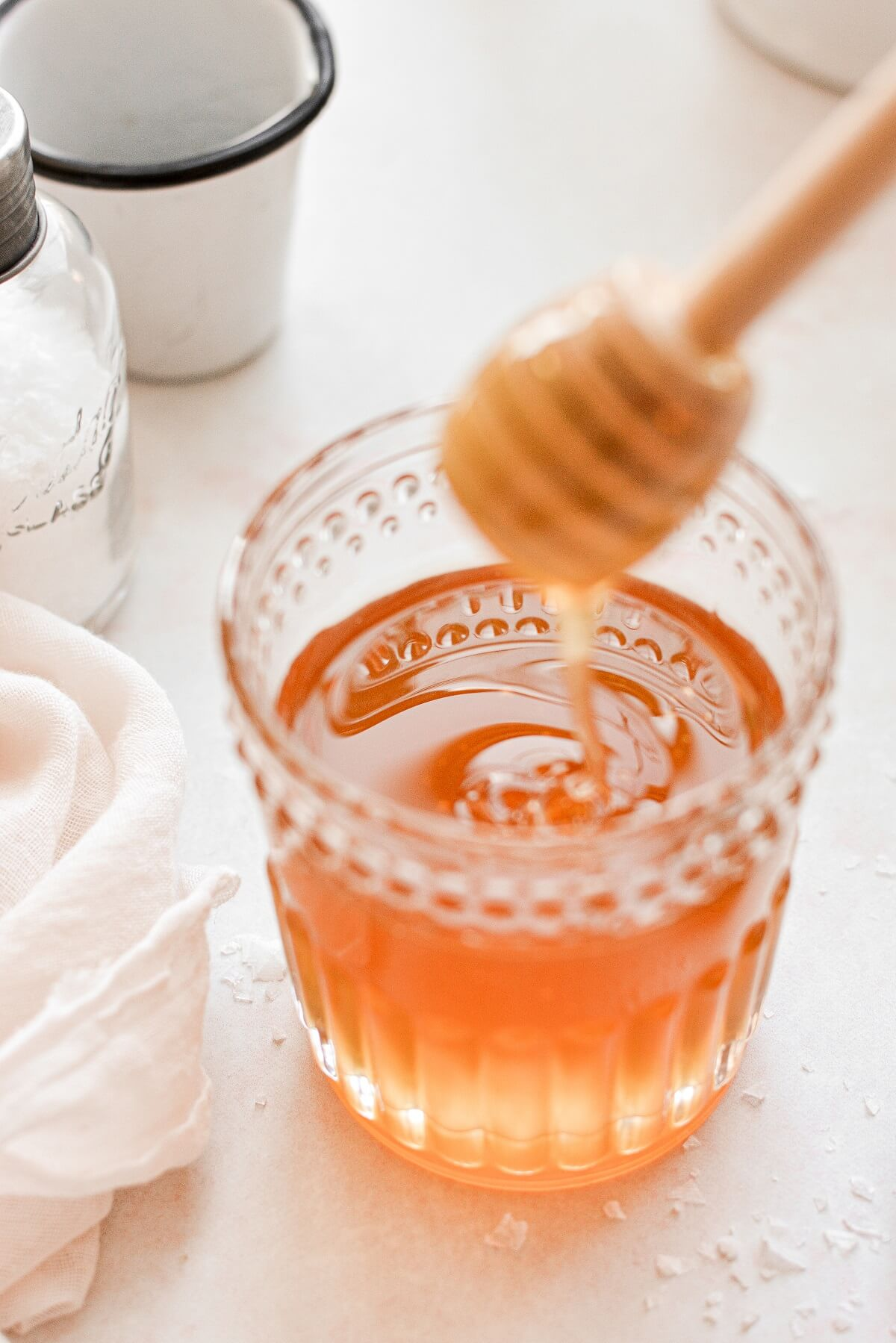 Honey drizzling off a honey dipper into a glass jar filled with honey.