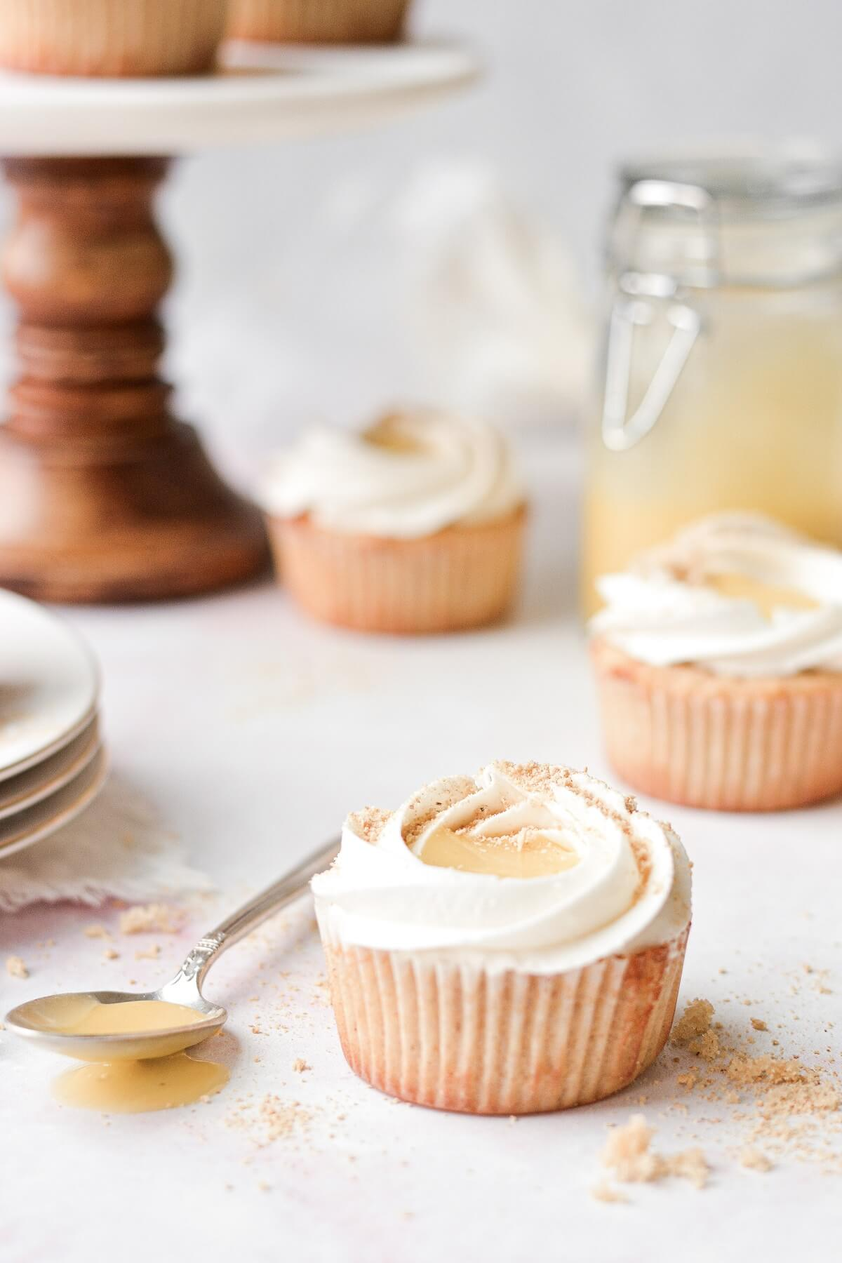 A key lime pie cupcake, next to a spoonful of lime curd.