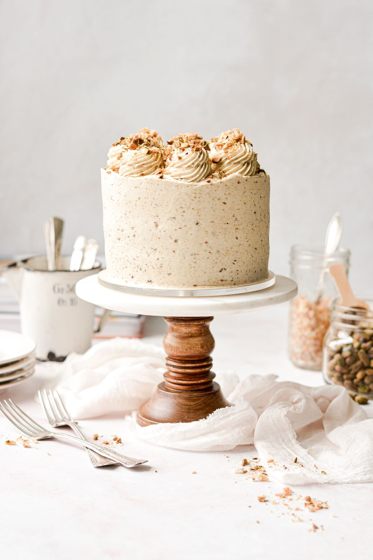 Orange pistachio layer cake on a wood and marble cake stand.