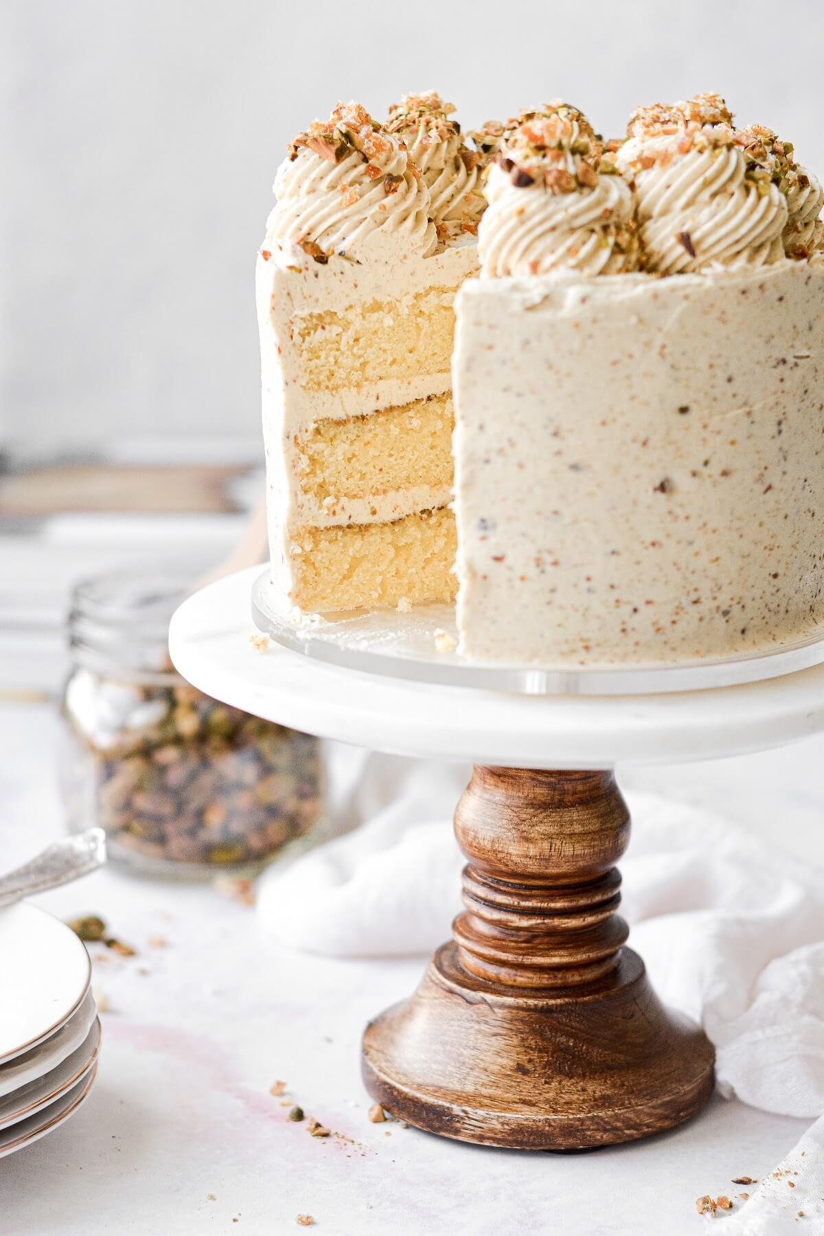 An orange pistachio layer cake, with one slice cut.