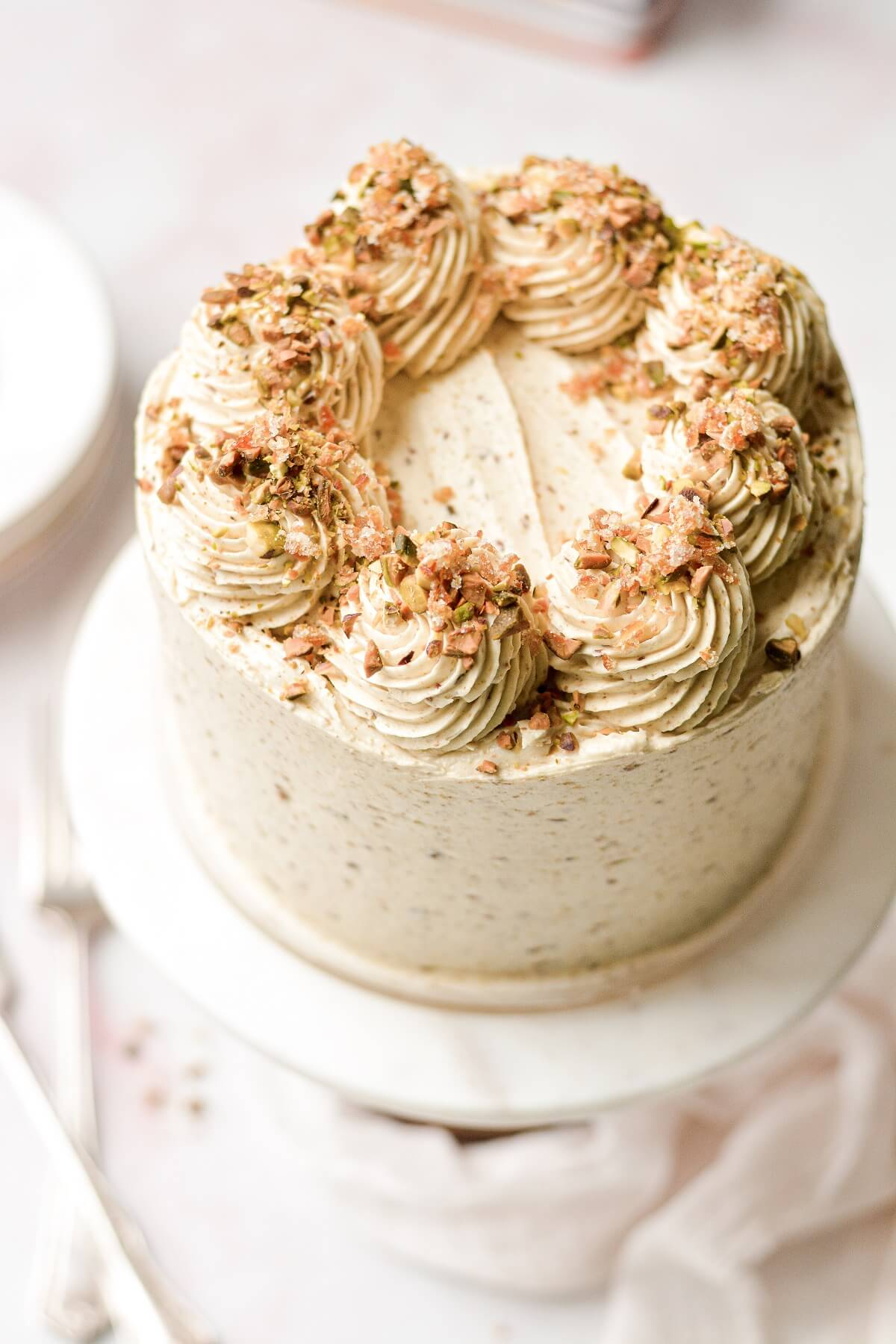 Orange pistachio layer cake, topped with swirls of buttercream, crushed pistachios and candied orange peel.