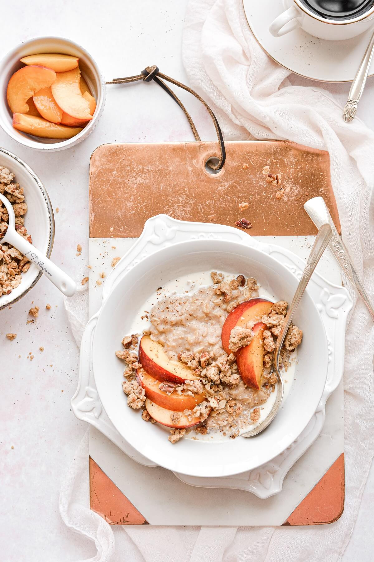 Peach crisp oatmeal, next to a bowl of sliced peaches and a bowl of crumble topping.