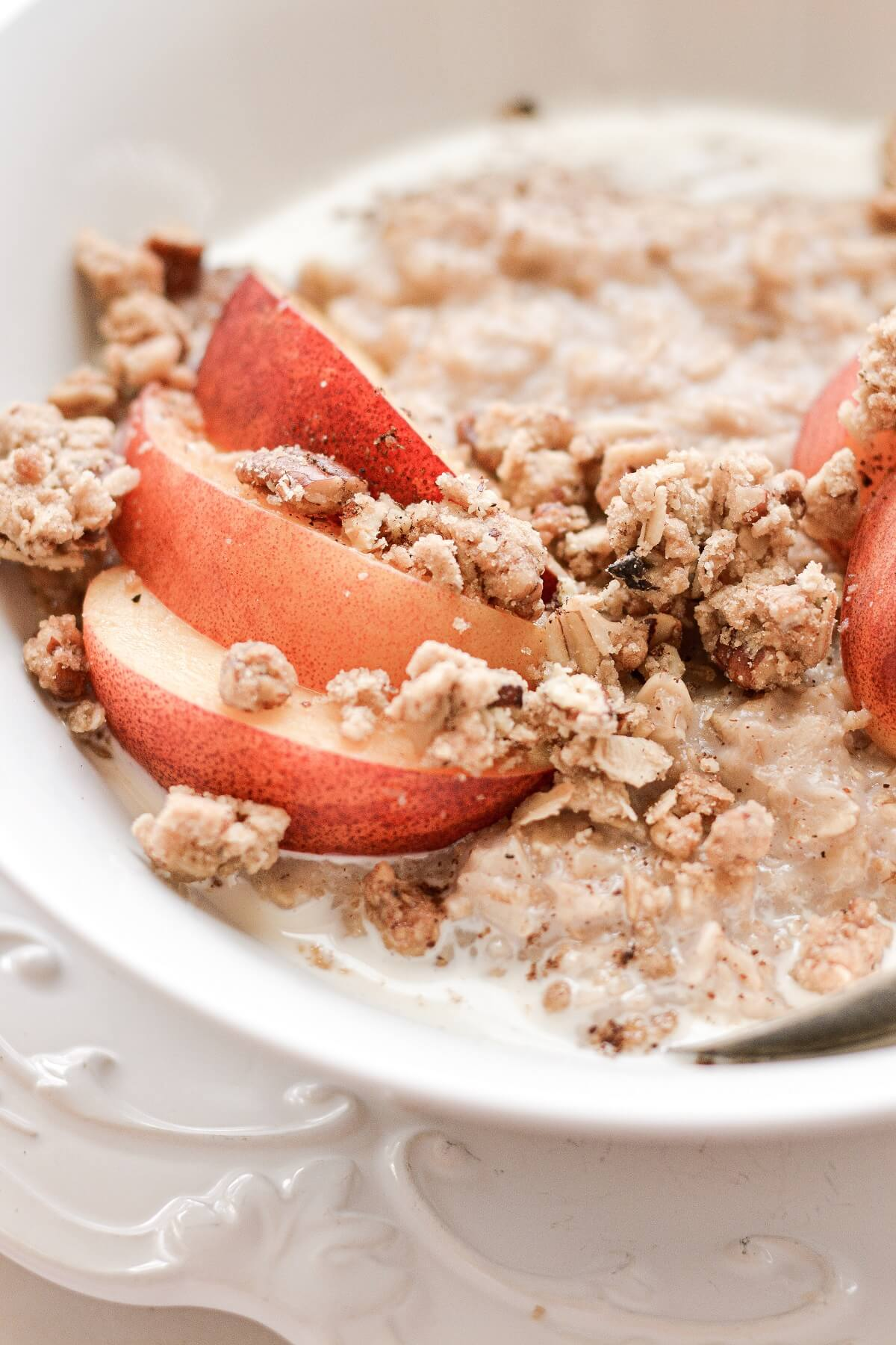 A bowl of oatmeal topped with sliced peaches and crumble topping.