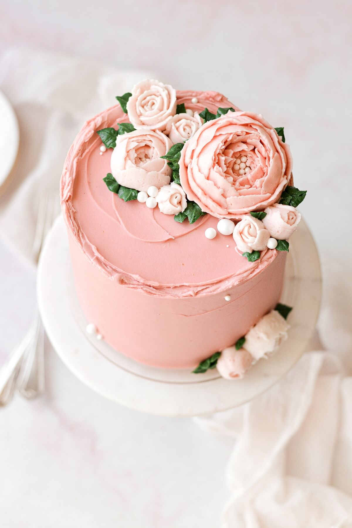 A layer cake frosted with pink buttercream and buttercream flowers.