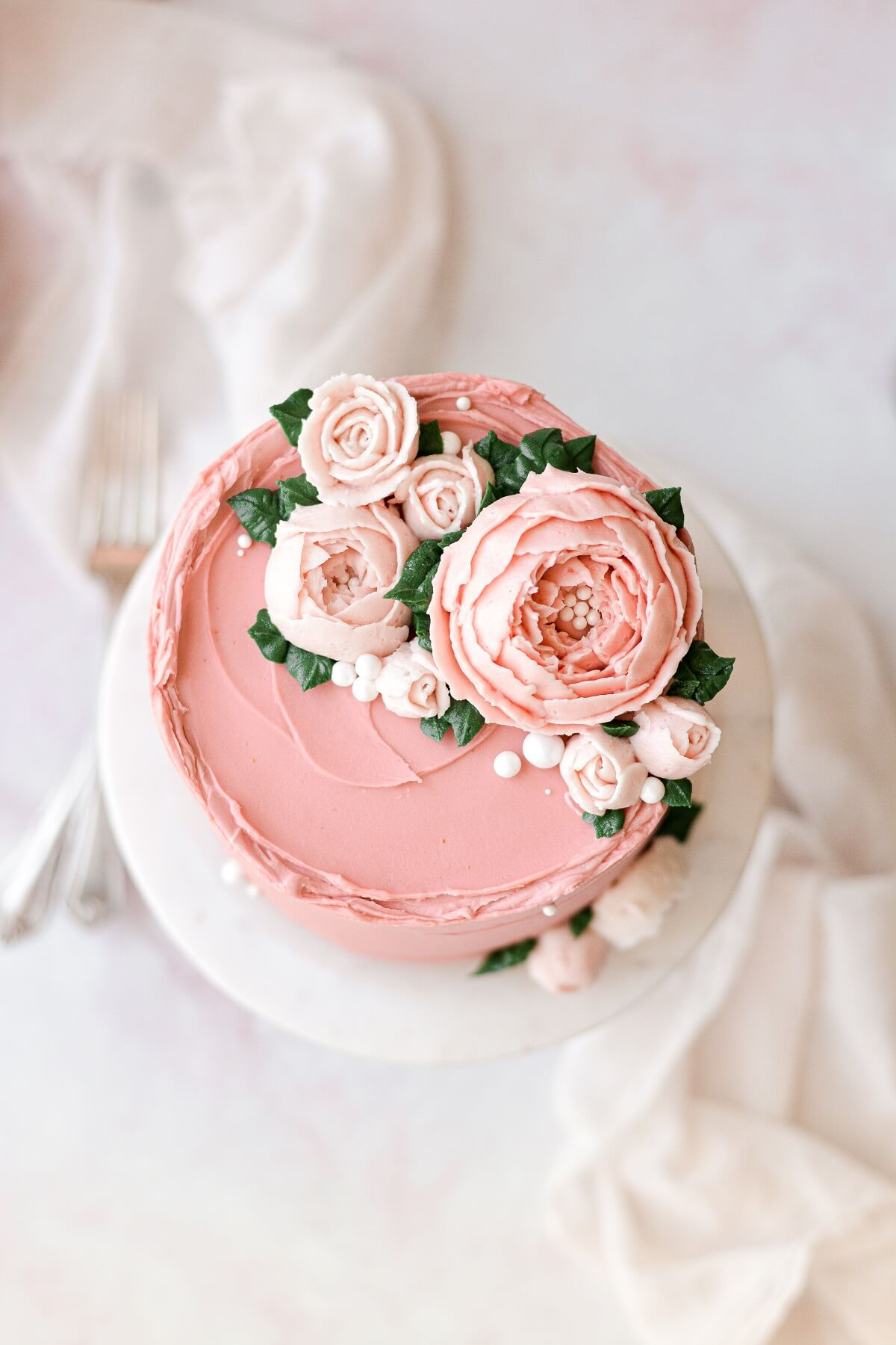 Buttercream flowers on a pink frosted cake.