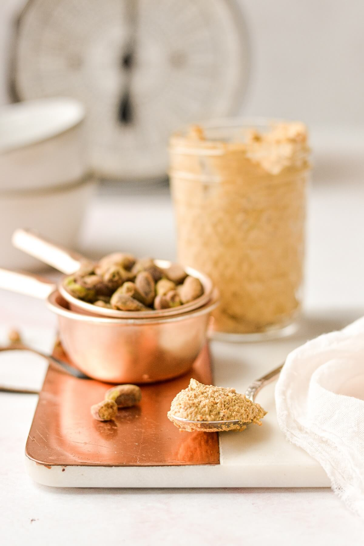 A jar of pistachio butter, next to pistachios and a spoon resting on a serving board.