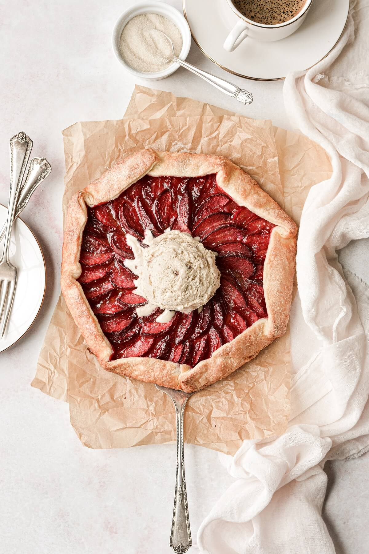 Plum galette on brown paper, topped with ice cream.