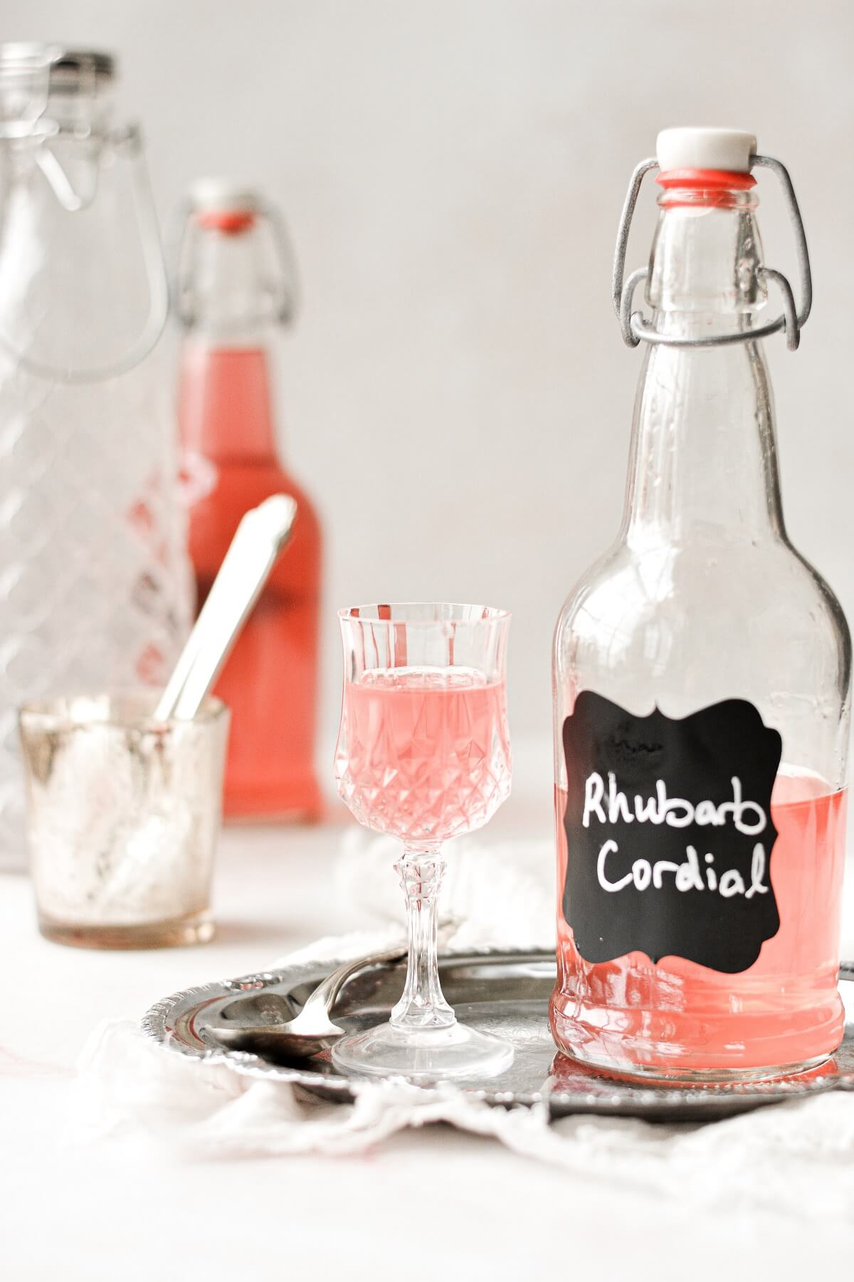 A bottle of homemade rhubarb cordial next to a small cordial glass.