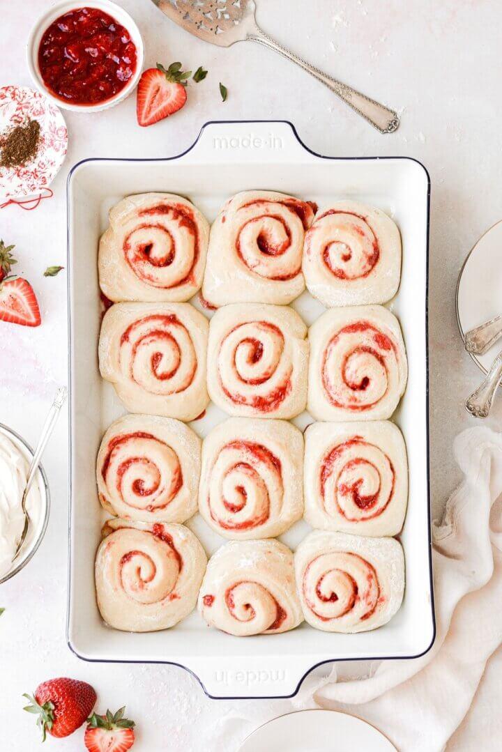 Twelve strawberry rolls in a baking pan.