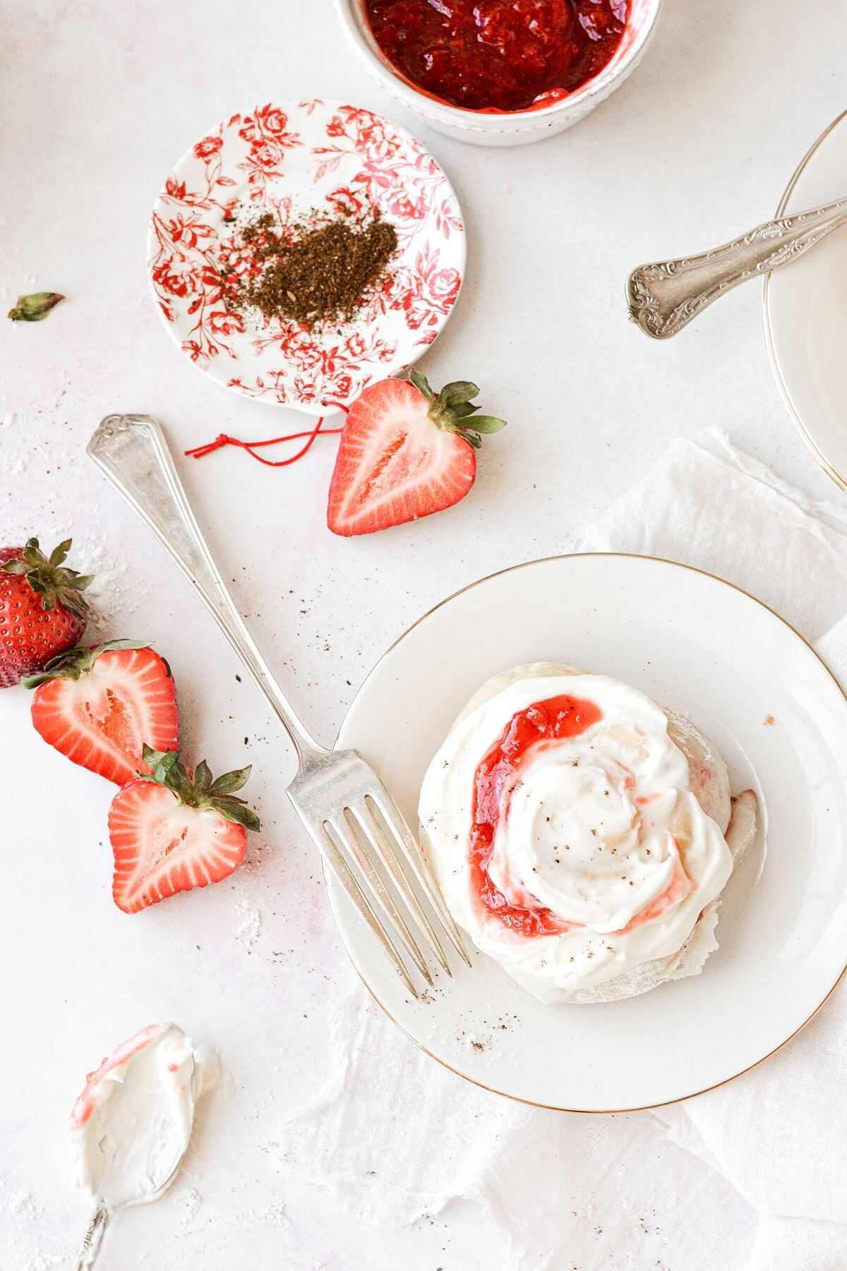 A strawberry roll with cream cheese frosting.