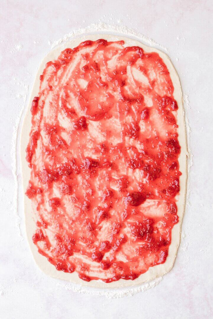 Dough spread with strawberry jam.