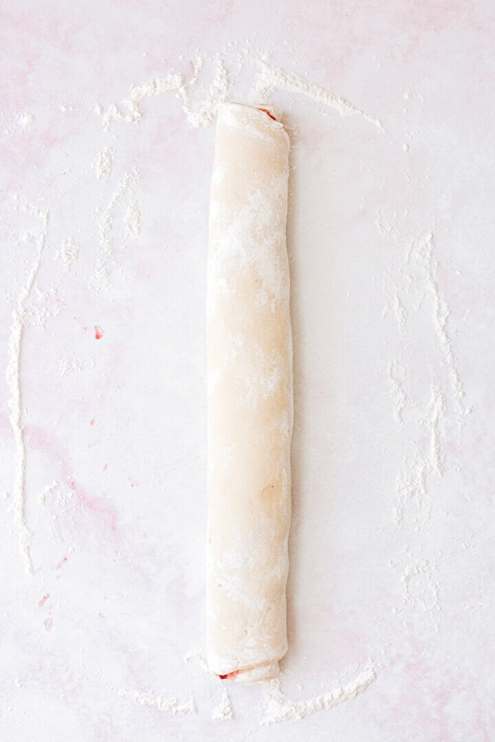 Dough, spread with strawberry jam, and rolled up.