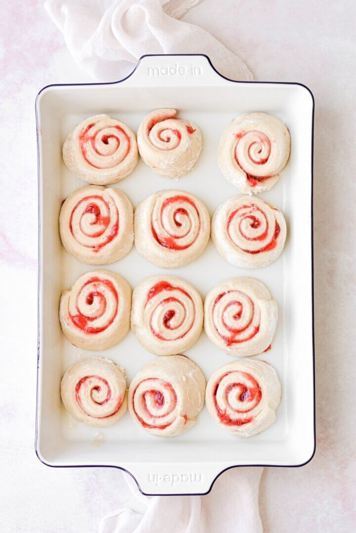 Strawberry rolls in a pan, ready to be baked.