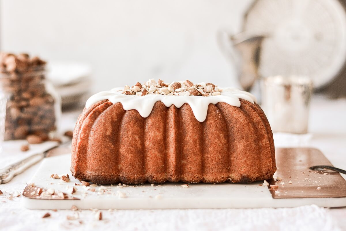 Almond pound cake with white icing dripping down.