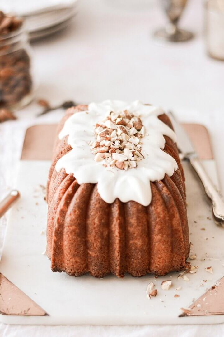A loaf of almond pound cake with almond icing and chopped almonds.