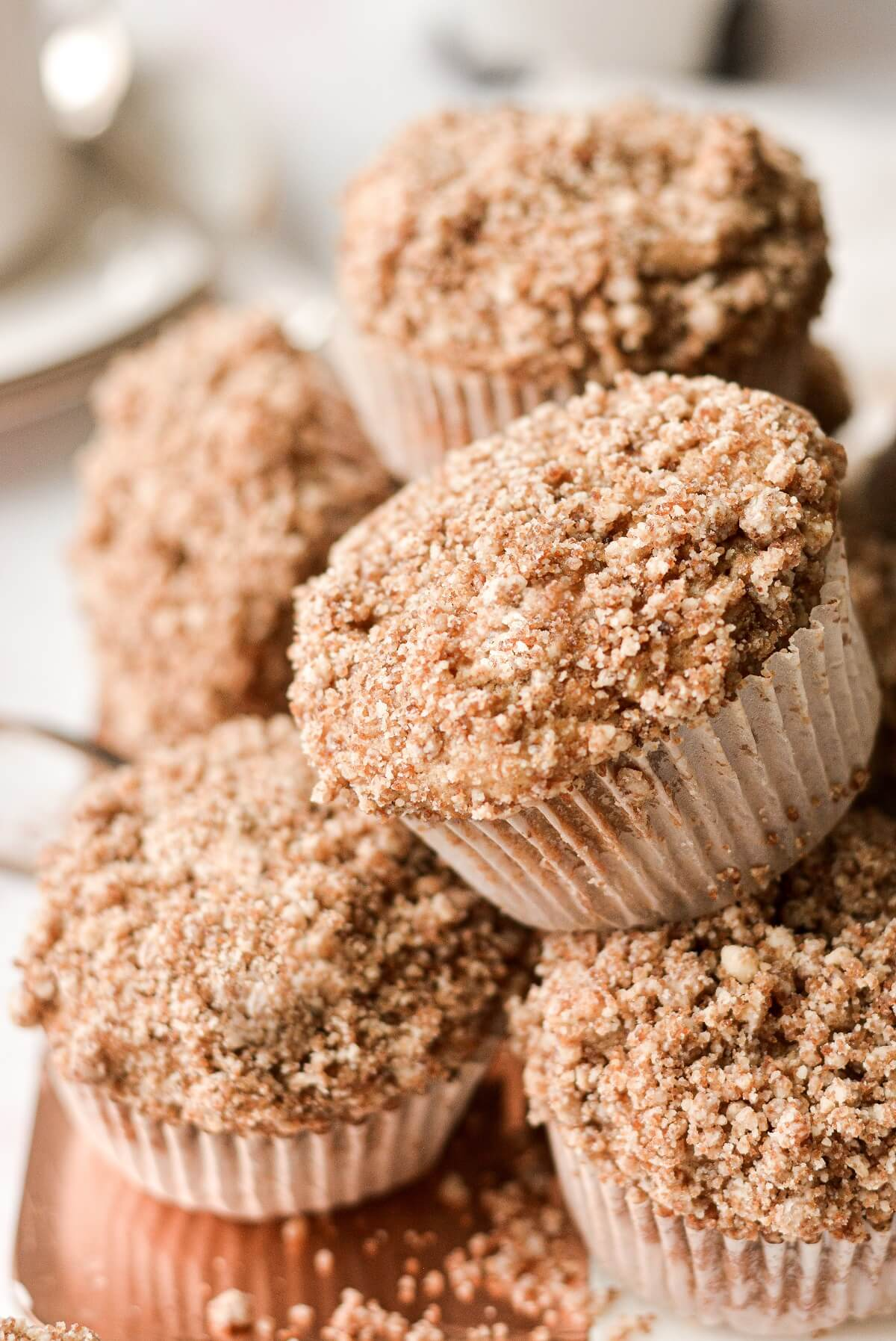 Apple spice muffins with crumb topping on a serving board.