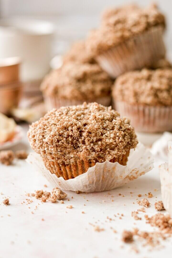 An apple spice muffin with crumb topping, with the wrapper pulled back.