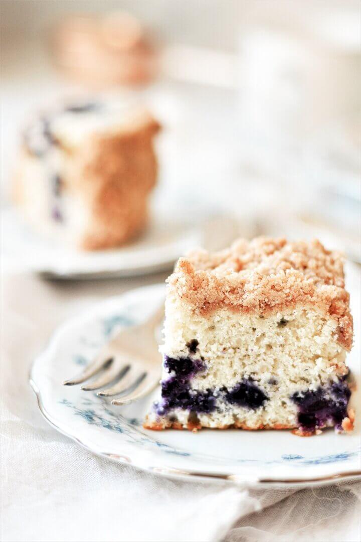 Slices of blueberry buckle coffee cake on blue flowered plates.